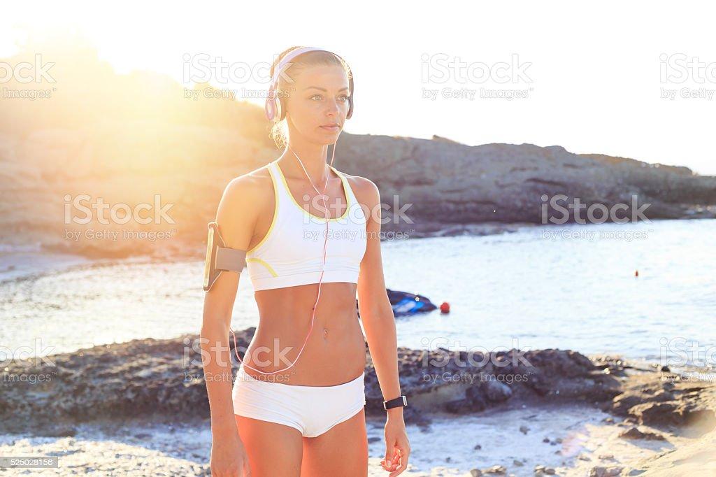 Sport woman with headphones resting on beach stock photo