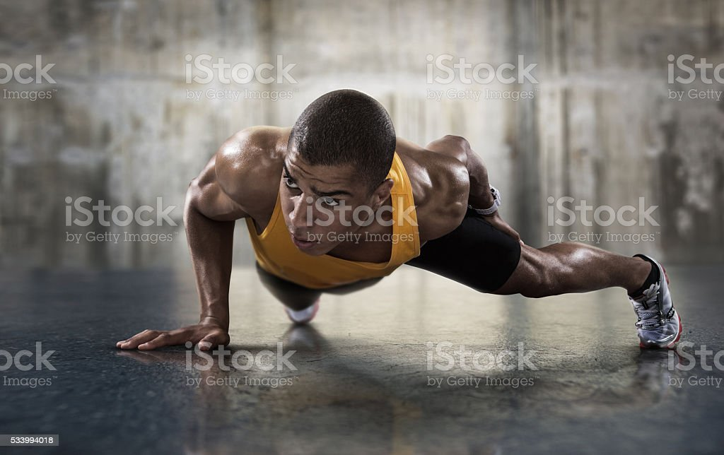 Sport. Young athletic man doing push-ups. stock photo