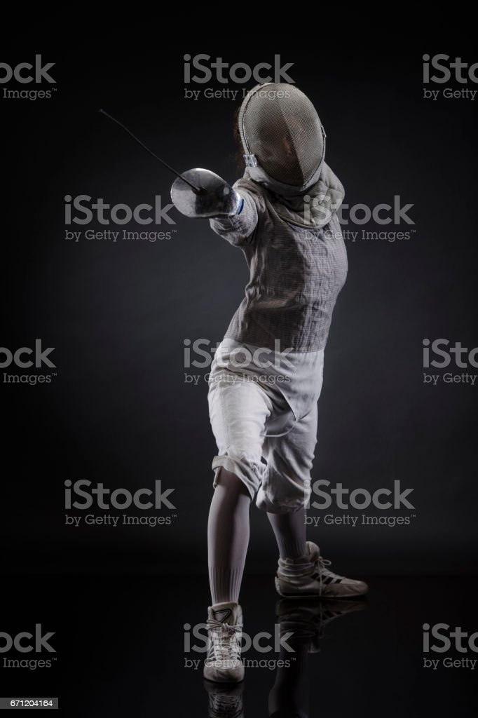 Sporting Women practicing Fencing sport  Women in sport Young woman Fencer standing in fencing pose   Dark grey background stock photo