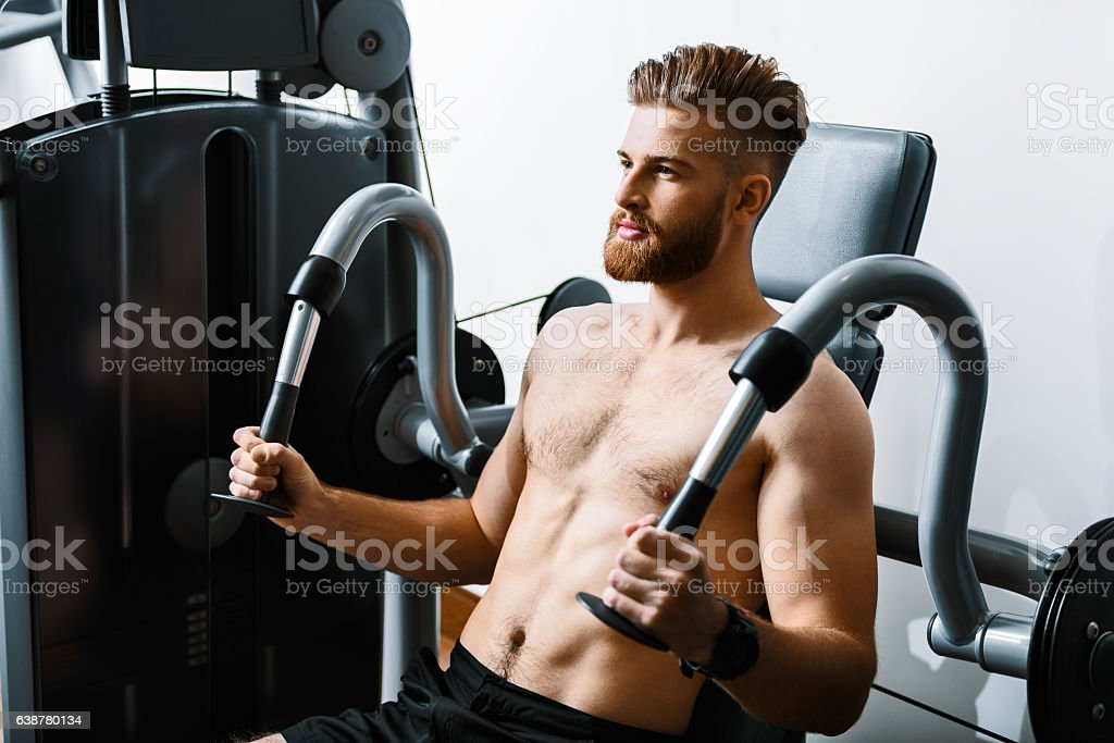 Sportive assured man in gym stock photo