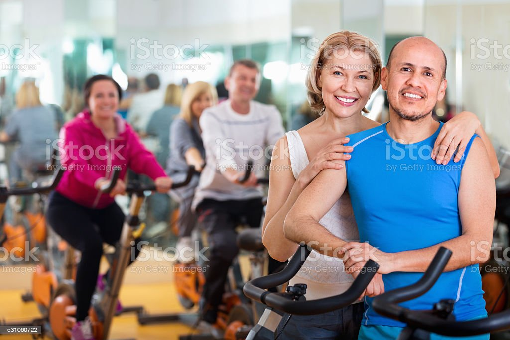 Sportive couple in a fitness club with friends stock photo