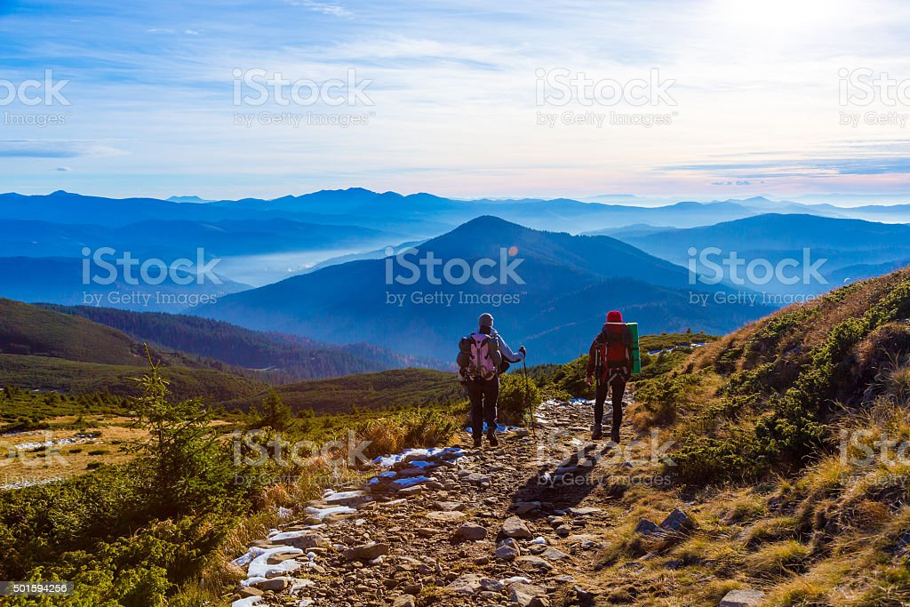 Sportive Couple walking on rural Road foggy Mountains Sunset stock photo