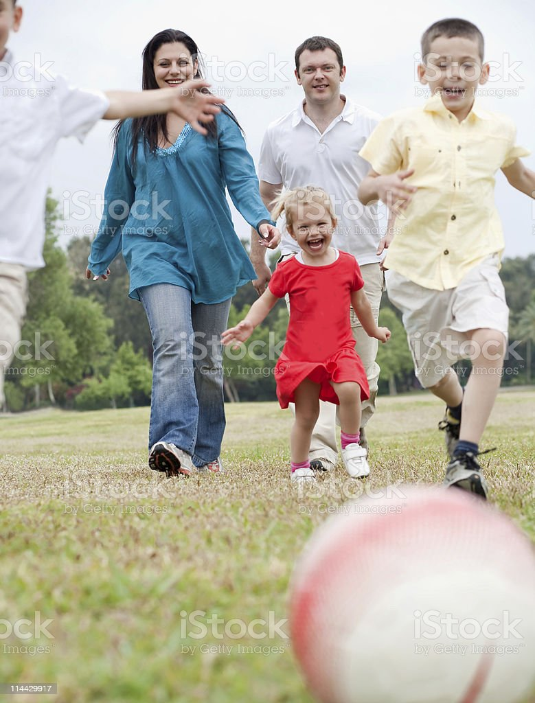 Sportive family playing football on the green lawn royalty-free stock photo