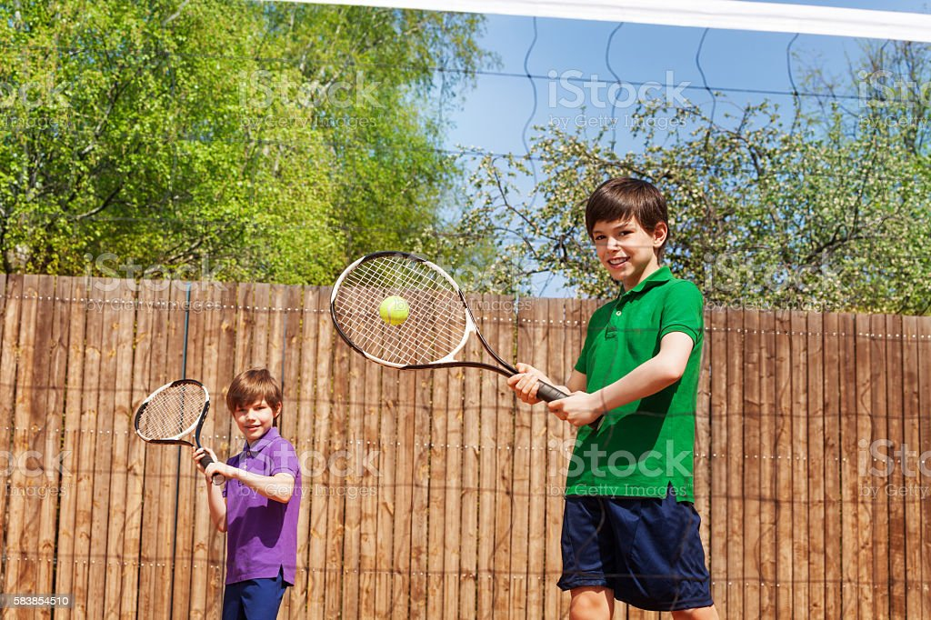 Sportive kid boy hitting forehand in tennis stock photo