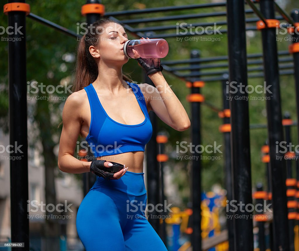 Sportive woman drinking vitamin water at the street gym stock photo