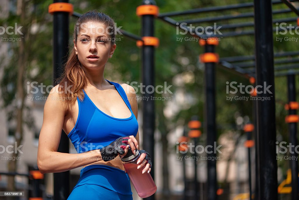 Sportive woman posing with bottle of water at the street stock photo
