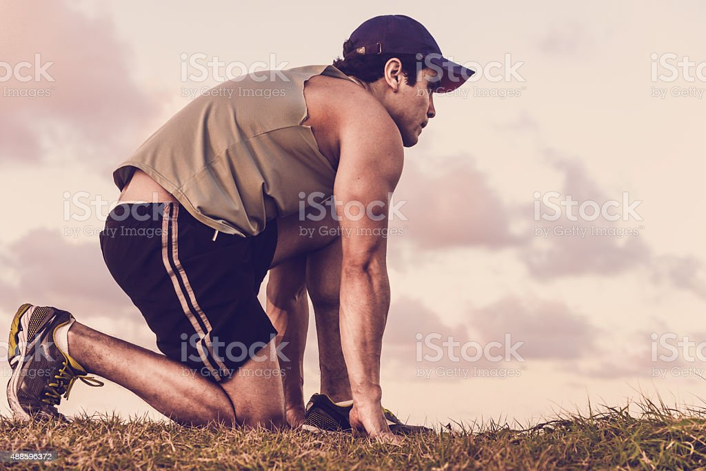 sportman with cap in start position for sprint stock photo