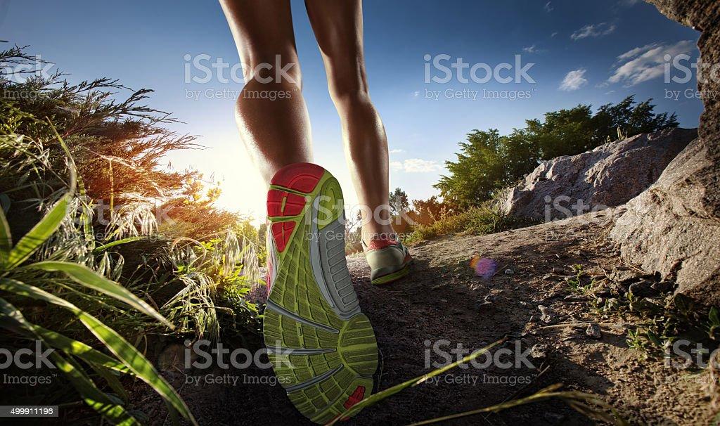 Sports background. Runner feet running on path. Closeup on shoe. stock photo
