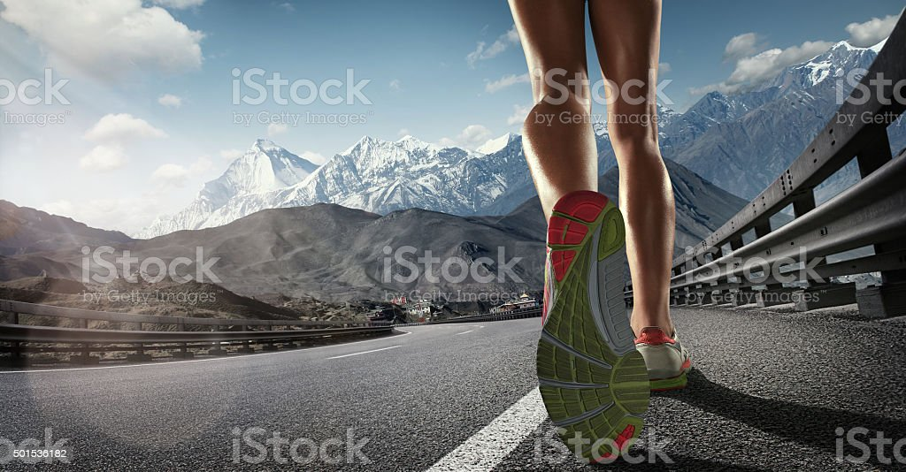 Sports background. Runner feet running on the road. Closeup on shoe stock photo