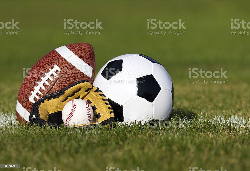 Sports balls on the field with yard line. Soccer ball, American...