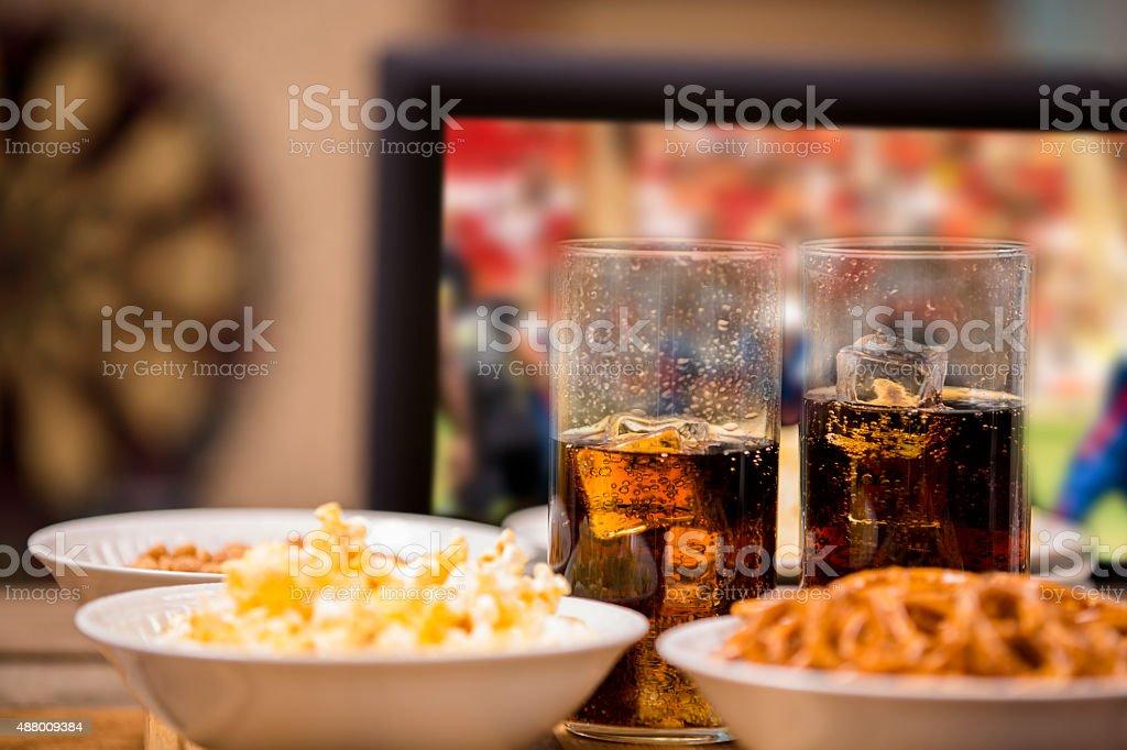 Sports bar. Popcorn, pretzels, soda, dartboard.  Football game on TV. stock photo