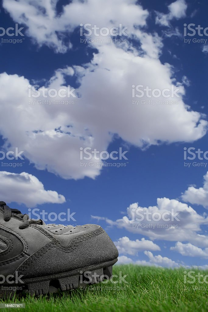 Sports Cleat on grass with sky background royalty-free stock photo