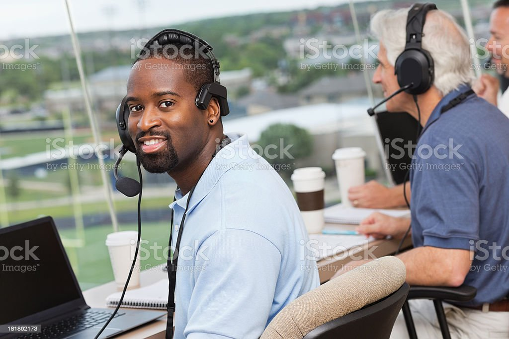Sports commentator wearing headset in press box at stadium stock photo