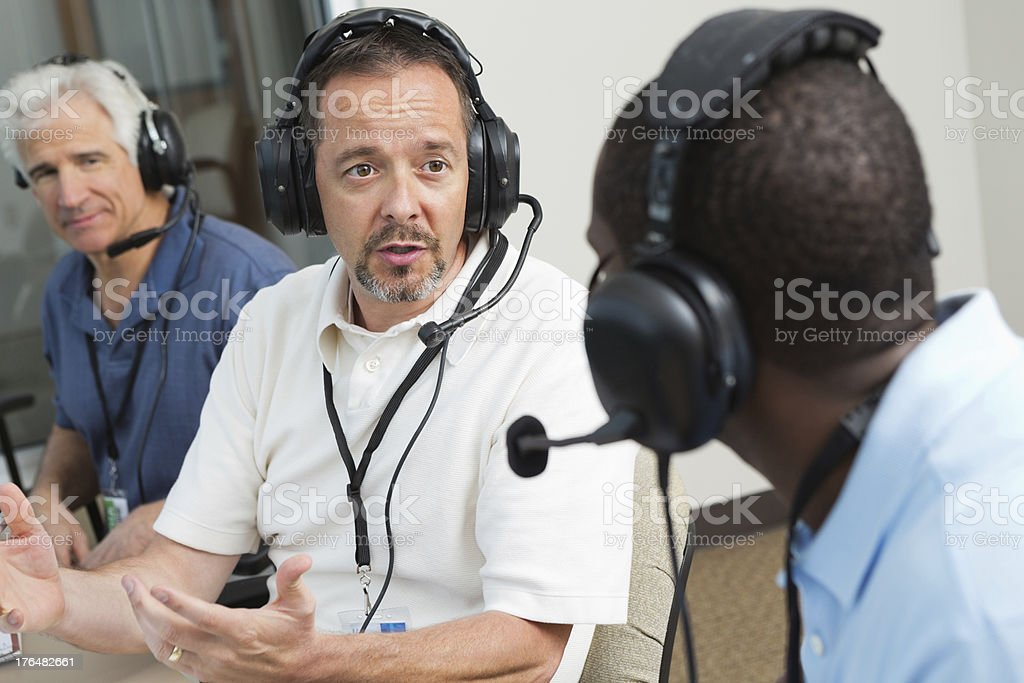 Sports commentators and journalists discussing game in press box stock photo