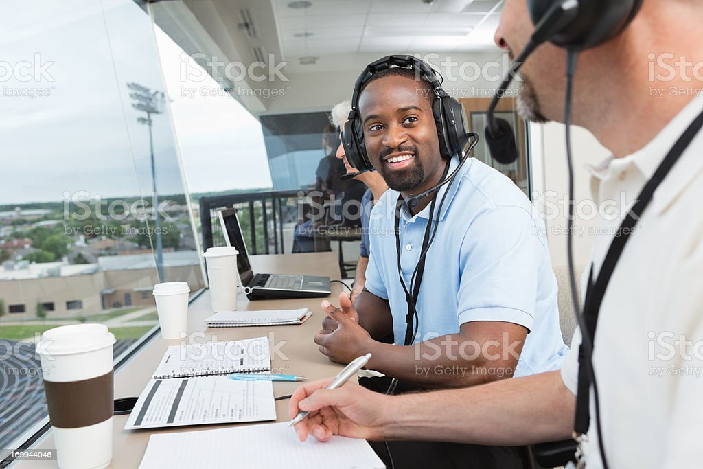 Sports commentators and other media covering game in press box stock photo