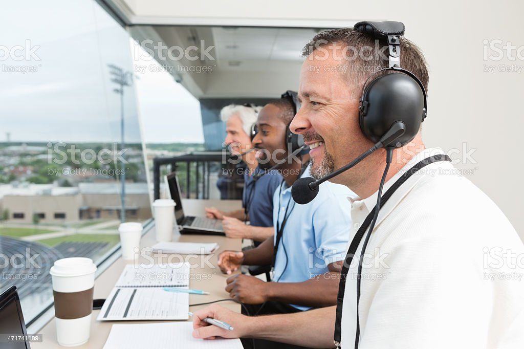 Sports commentators covering game from stadium press box stock photo