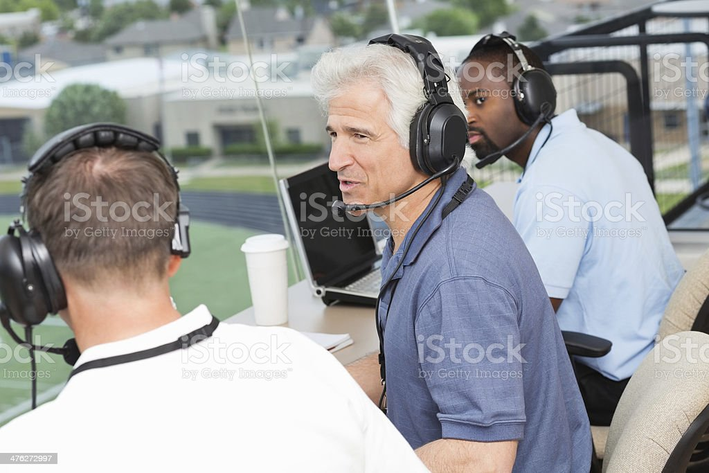 Sports commentators discussing football game from press box at stadium stock photo