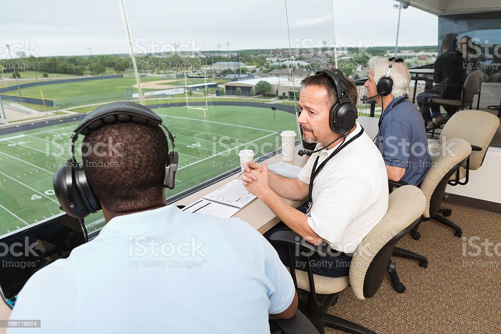 Sports Commentators discussing football game in the press box stock photo