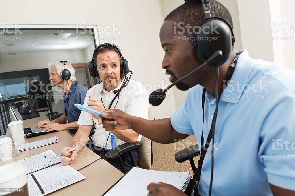 Sports Commentators discussing game in the media press box stock photo