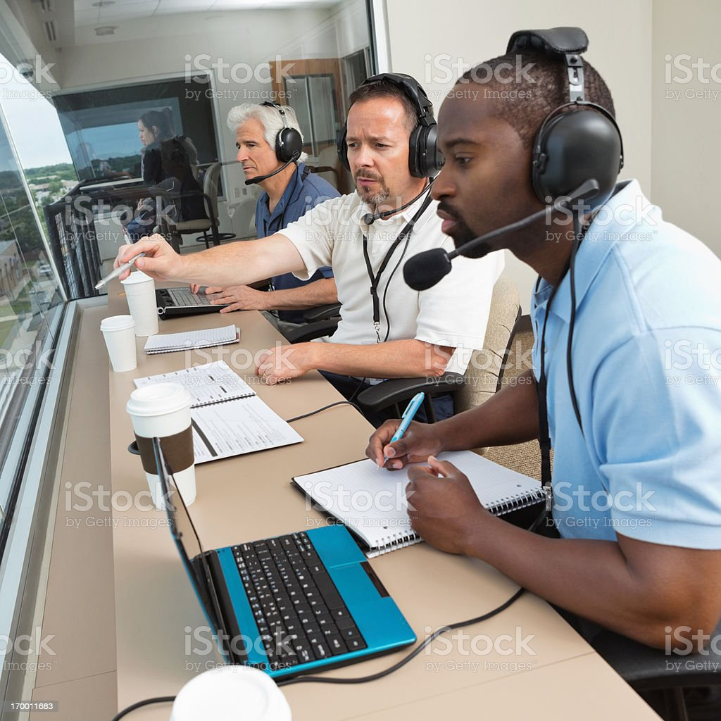 Sports commentators discussing play during game from stadium press box stock photo