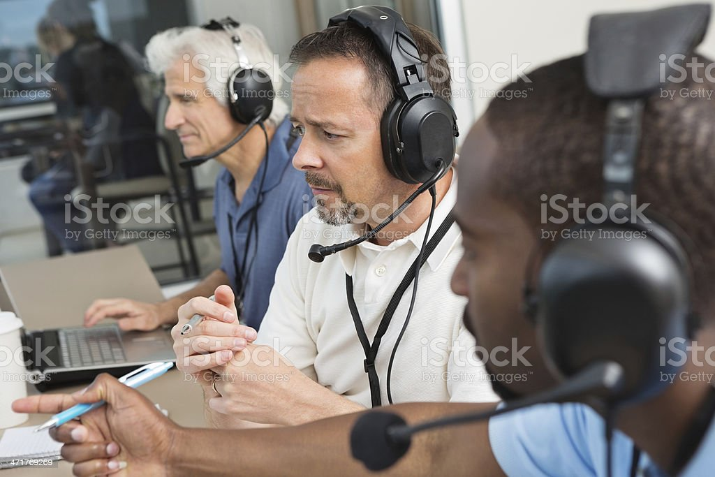 Sports commentators watching football game from press box stock photo