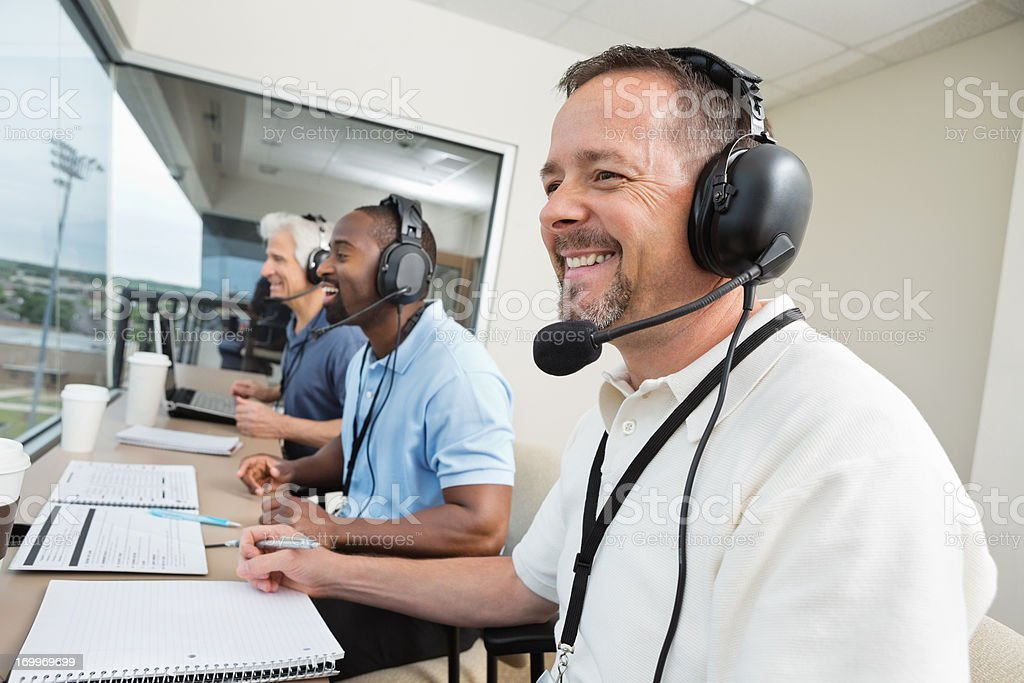 Sports commentators wearing headsets; reporting from stadium press box stock photo