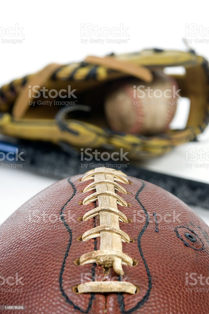 A well used football, baseball and bat. Isolated on white.