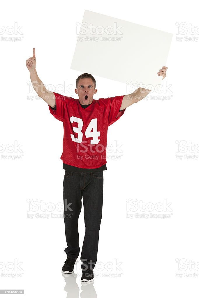 Sports fan holding a placard and cheering stock photo