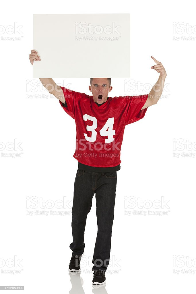 Sports fan holding a placard and shouting stock photo