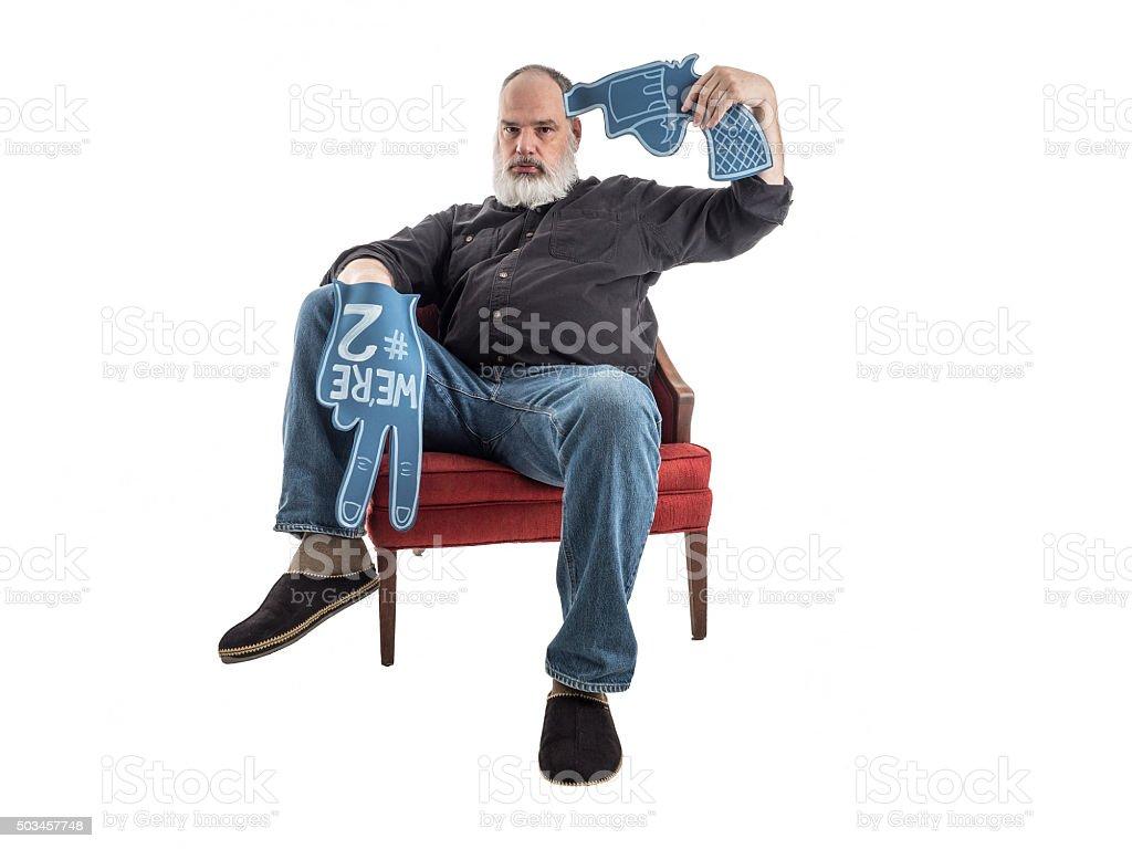 Sports Fan with Foam Finger Holds Foam Gun to Head stock photo