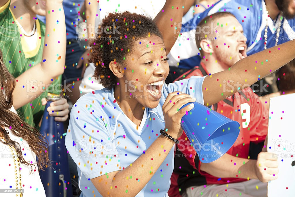 Sports: Fans cheer for team during local sporting event. Confetti. stock photo