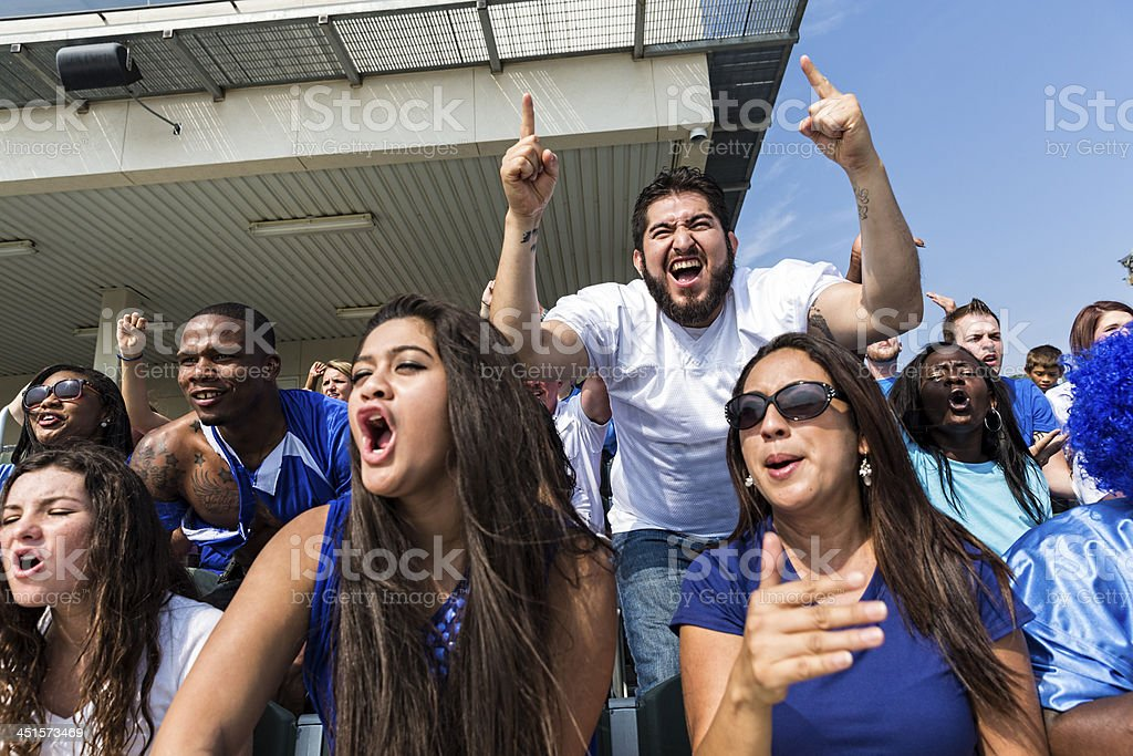 Football fans screaming and yelling for their football team.