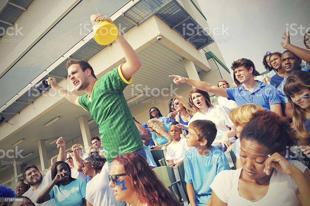 Sports fans heckling fan from opposing team in bleachers stock photo