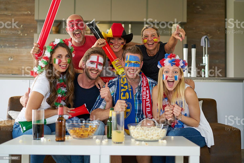 sports fans in front of tv stock photo
