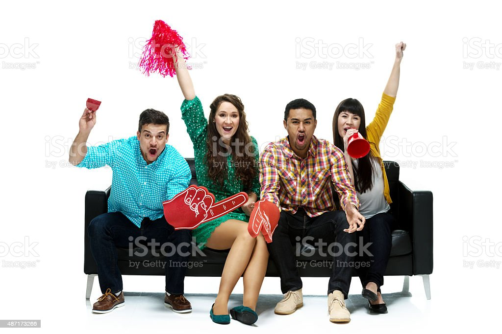 Sports fans on couch and cheering stock photo