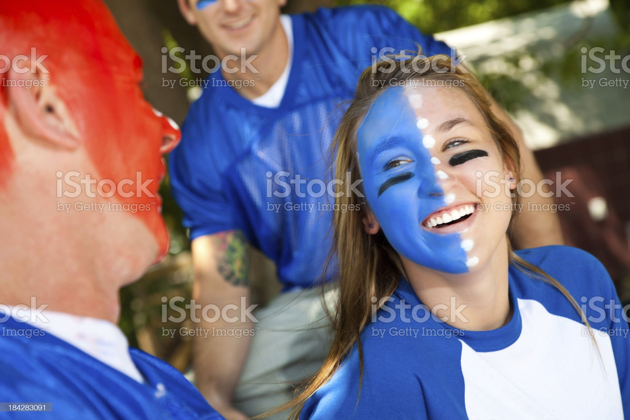 Sports fans with painted faces laughing at tailgate party. royalty-free stock photo