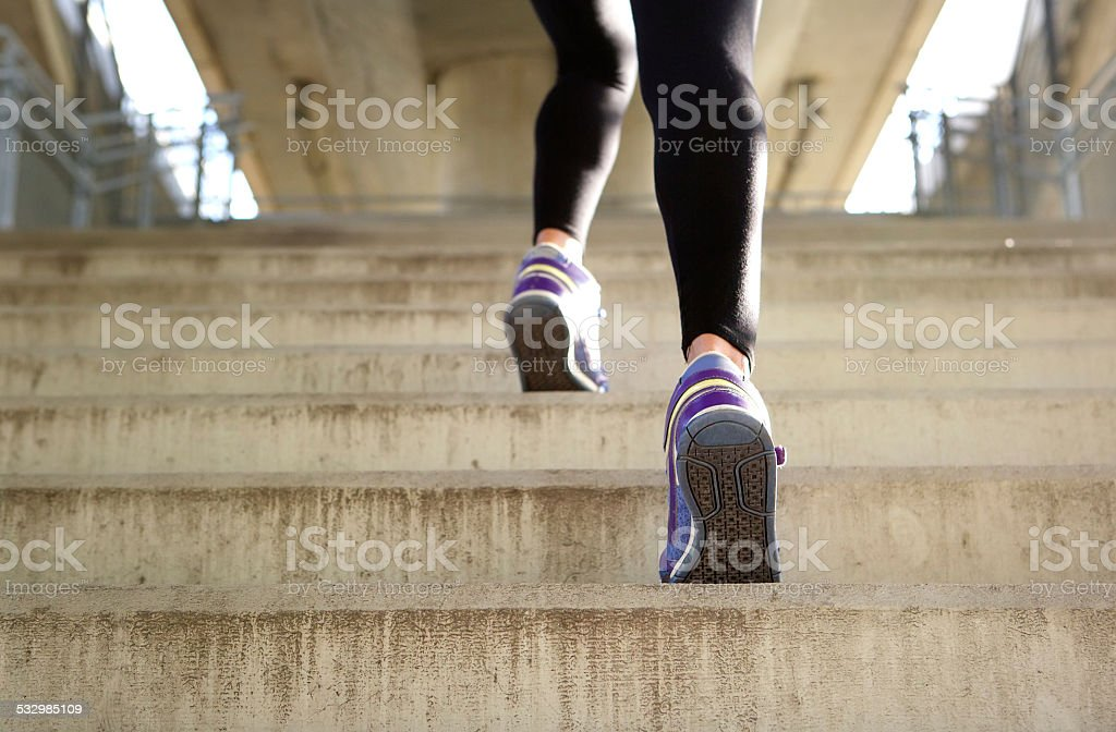 Sports female running up stairs stock photo
