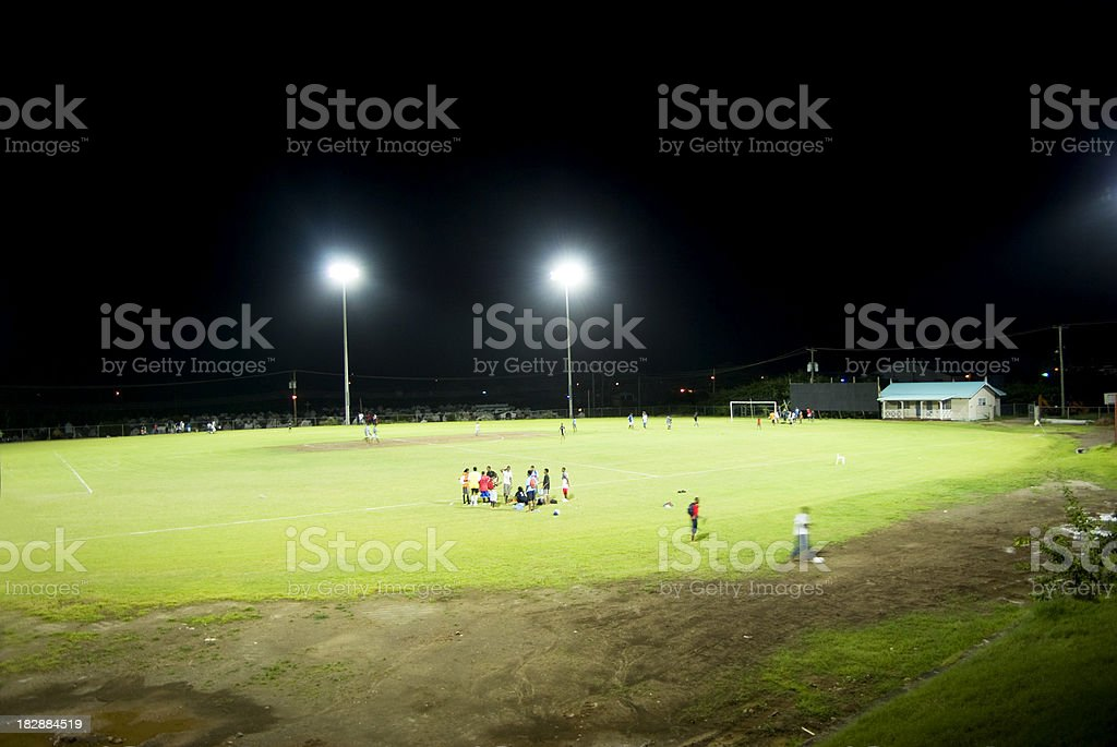 sports field and athletes under floodlights stock photo