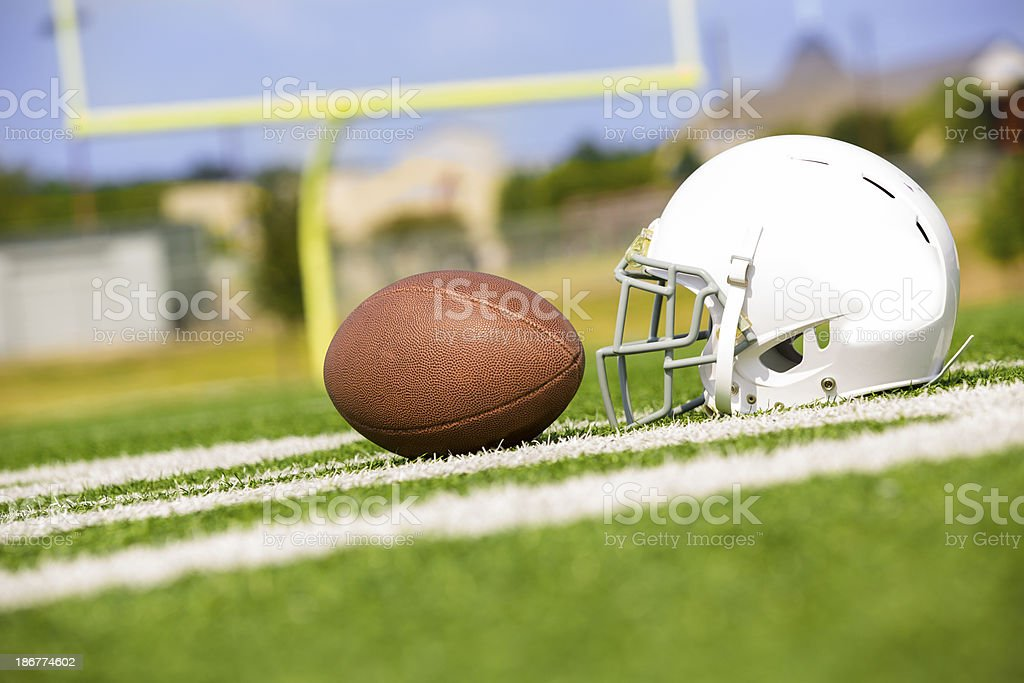 Sports:  Football and helmet on playing field. stock photo