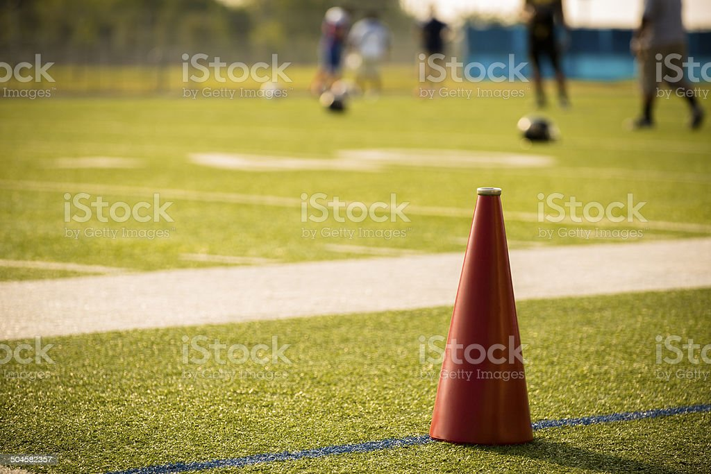 Sports: Football field with megaphone foreground. Players background. royalty-free stock photo