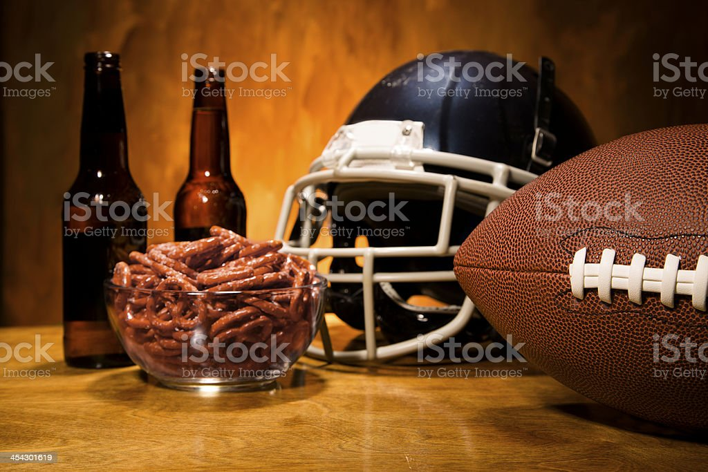 Sports:  Football helmet, ball on table.  Pretzels and beer. Superbowl. stock photo