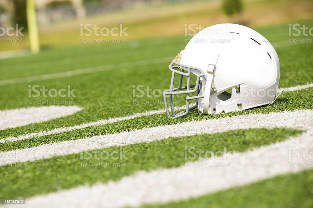Sports:  Football helmet on playing field.  Yard markers foreground. royalty-free stock photo