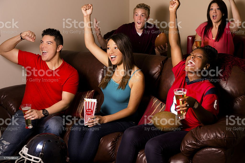Sports: Friends cheer after their football team scores. Media room. royalty-free stock photo