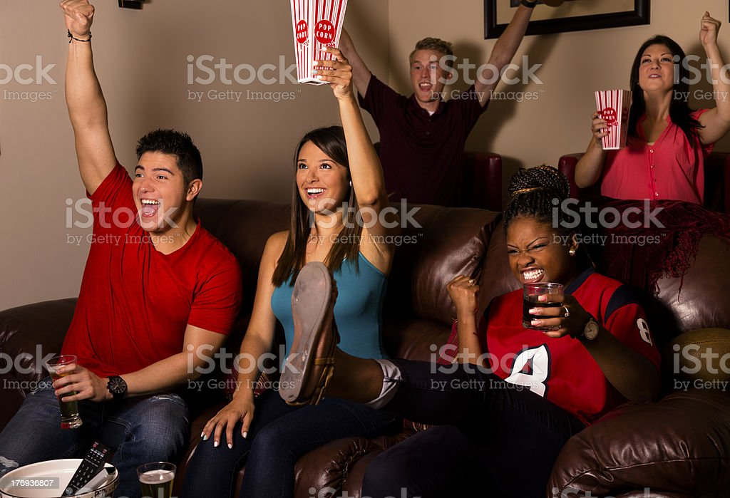 Sports: Friends cheer after their team scores. Media room. royalty-free stock photo