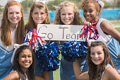 Sports: Group of high school cheerleaders with 'Go Team' sign.