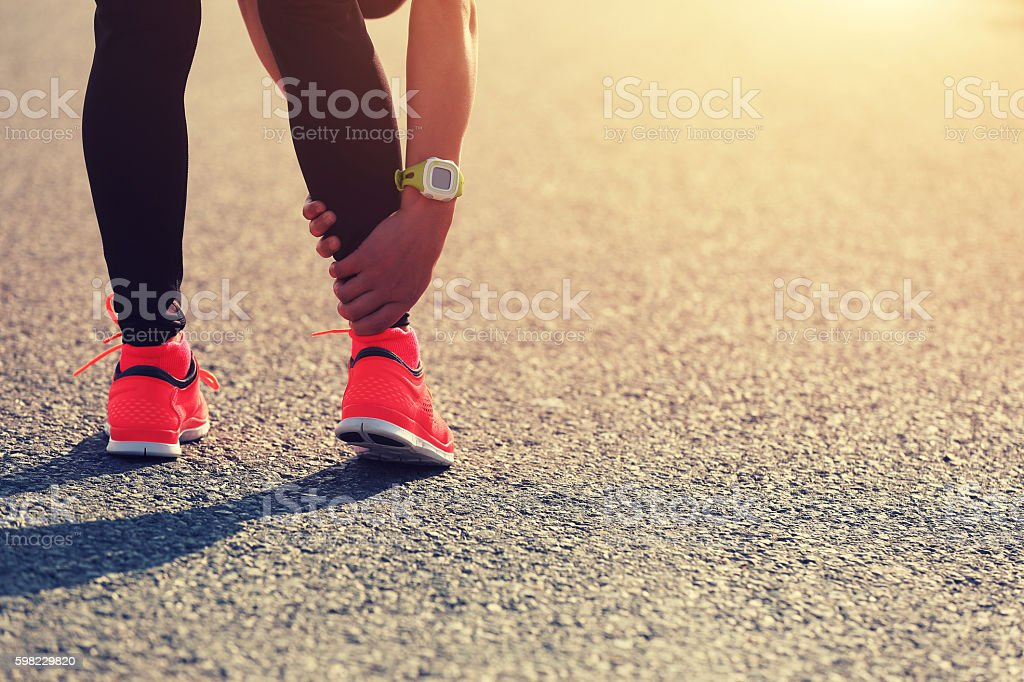 sports injury on young woman runner leg stock photo