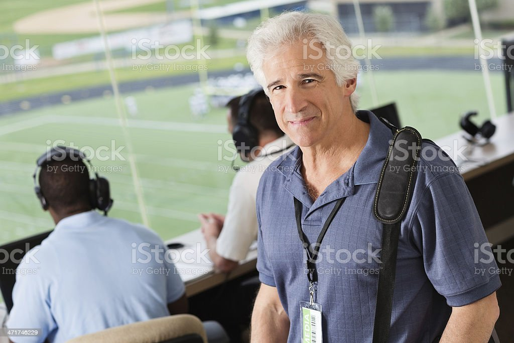 Sports journalist reporting from press box at stadium stock photo