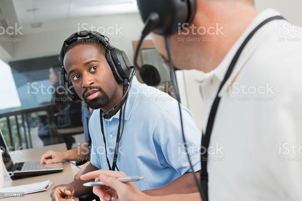 Sports journalist watching game from press box at football stadium stock photo