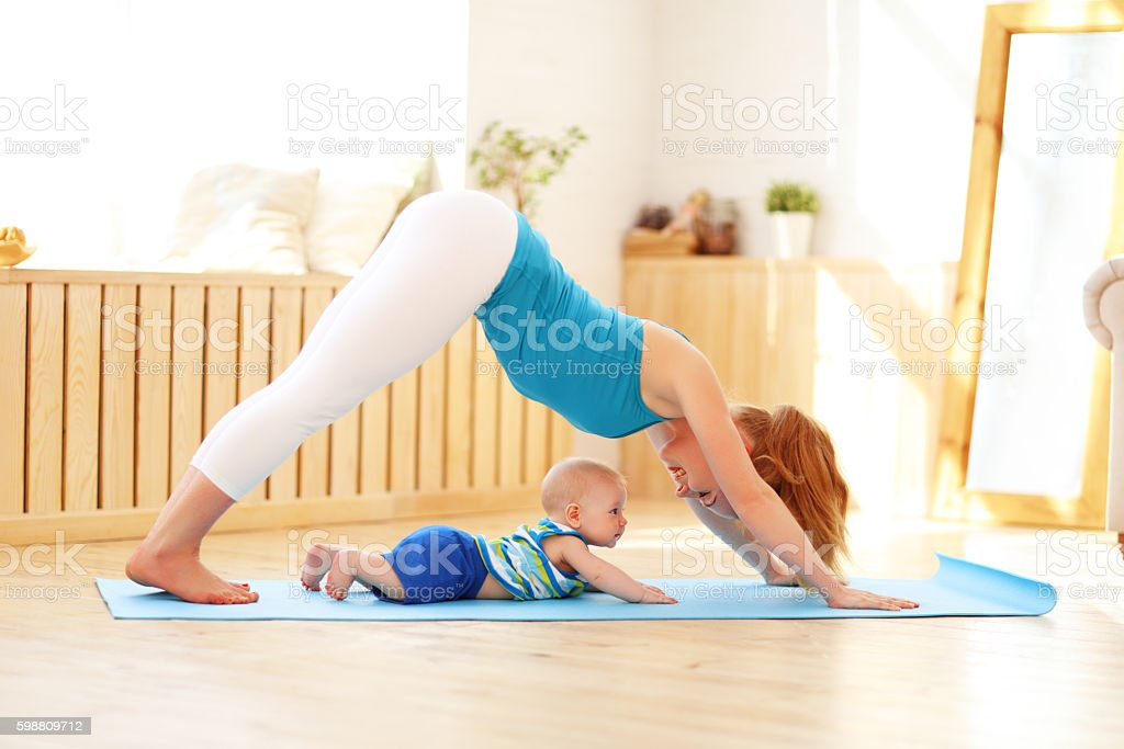 sports mother is engaged in fitness and yoga with baby stock photo