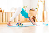sports mother is engaged in fitness and yoga with baby
